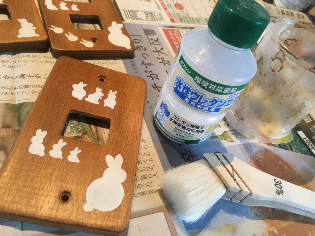 デコレーションしたコンセントプレートにニスを塗って表面保護する。